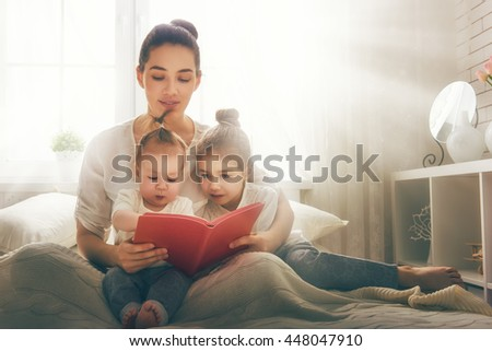 happy loving family. pretty young mother reading a book to her daughters - stock photo