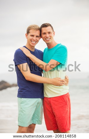 Happy loving gay couple on the beach - stock photo