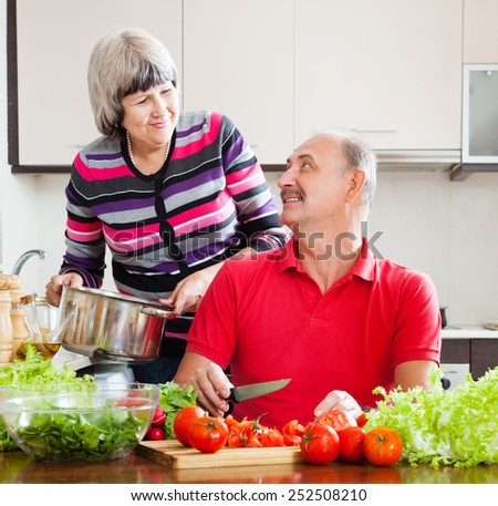 happy loving mature couple cooking with tomatoes in kitchen at home