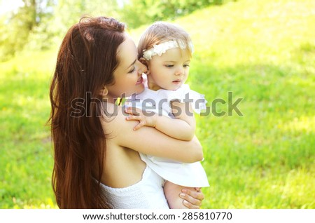 Happy loving mom and baby together outdoors in sunny summer day