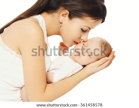 Happy loving mother kissing her baby holding on hands over white background