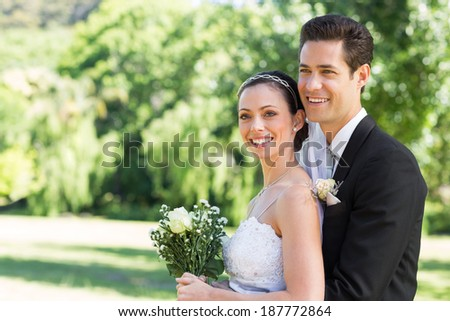 Happy loving newly wed couple looking away while standing in park - stock photo