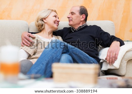 Happy loving pensioners enjoying company of each other and smiling - stock photo