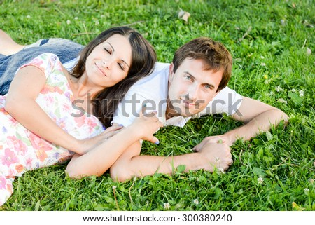 Happy loving pretty young couple outdoors having fun on sunny day. Handsome man and his pretty girlfriend posing outdoor, enjoying time together. Romance and love concept.