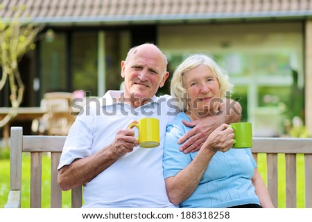 Happy loving senior couple drinking tea from big colorful mugs sitting on a wooden bench in the garden at the backyard of their house in front of fresh blooming magnolia tree - stock photo