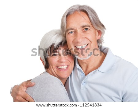 Happy loving senior couple standing in an intimate embrace isolated on white