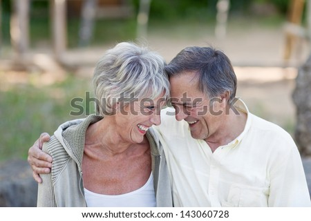 Happy loving senior couple with head to head smiling in park - stock photo