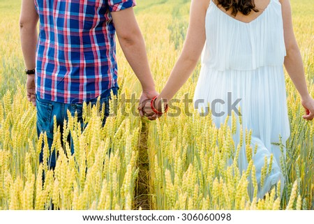 Happy loving young adult couple spending time on the field on sunny day outdoors. Handsome man and beautiful woman holding hands and running on wheat field.  Enjoying holiday together.  - stock photo