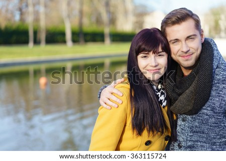 Happy loving young couple standing arm in arm alongside a canal smiling at the camera, with copy space - stock photo