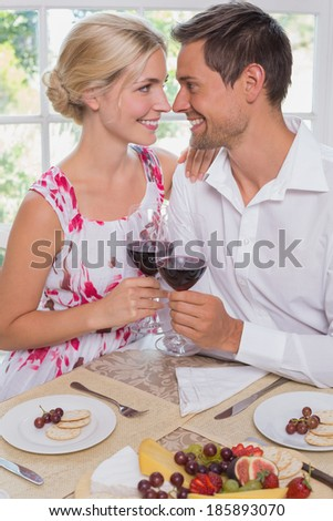 Happy loving young couple with wine glasses at dining table at home - stock photo