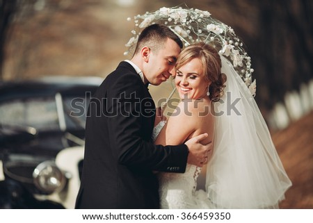 Happy luxury wedding couple kissing and embracing near retro car in autumn