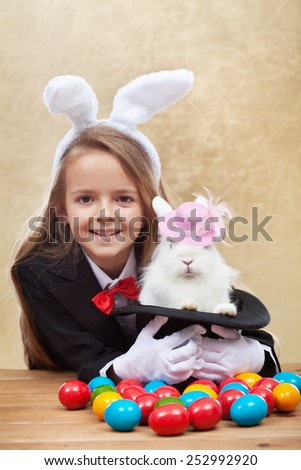 Happy magician girl holding cute easter bunny in magic hat - with colorful eggs- shallow depth of field - stock photo