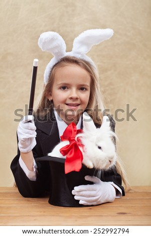 Happy magician girl wearing bunny ears holding white rabbit in a hat- shallow depth of field - stock photo
