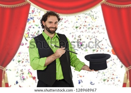 Happy magician with his baryte in the theater with a red curtain