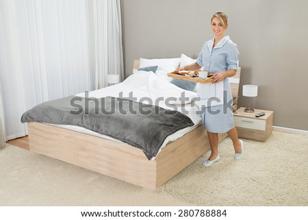 Happy Maid Carrying Breakfast Tray In Hotel Room - stock photo
