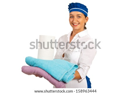 Happy maid holding clean towels and rolls of toilet paper isolated on white background - stock photo