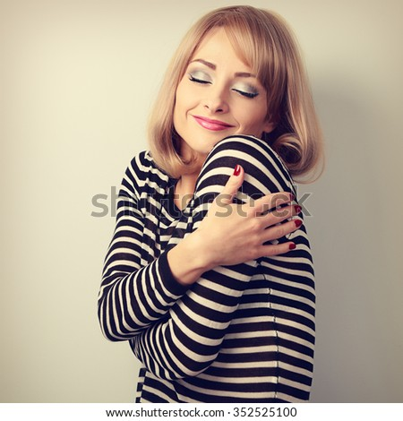Happy makeup blond woman hugging herself with natural emotion on enjoying face with close eyes. Love concept by yourself. Toned closeup portrait - stock photo