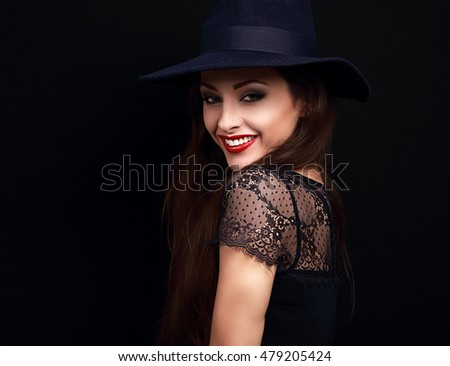 Happy makeup woman in fashion blue hat smiling toothy on dark black background