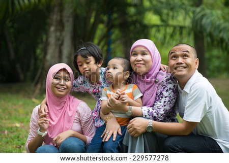 Happy Malay Asian Family enjoying family time together in the park - stock photo