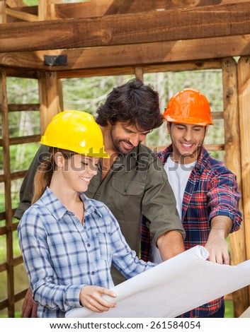 Happy male and female architects discussing over blueprint in wooden cabin at site - stock photo
