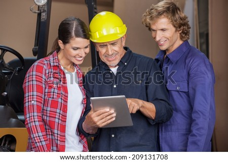 Happy male and female carpenters using digital tablet together in workshop - stock photo