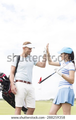 Happy male and female friends giving high-five at golf course - stock photo