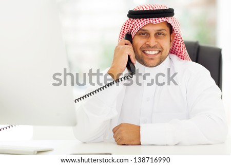happy male arab corporate worker talking on the landline phone
