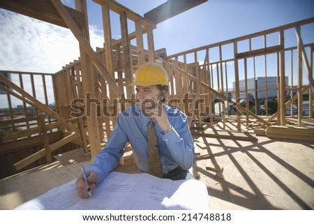 Happy male architect communicating through cell phone with blueprint at construction site - stock photo