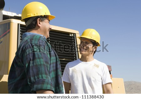 Happy male architects wearing hard hat at construction site