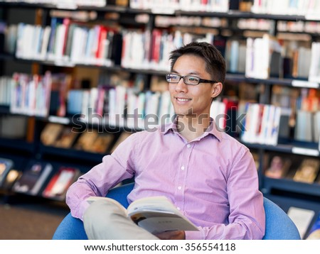 Happy male asian student holding books at the library - stock photo