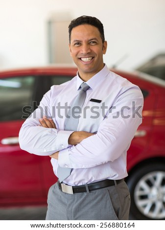 happy male car dealer principal inside showroom - stock photo