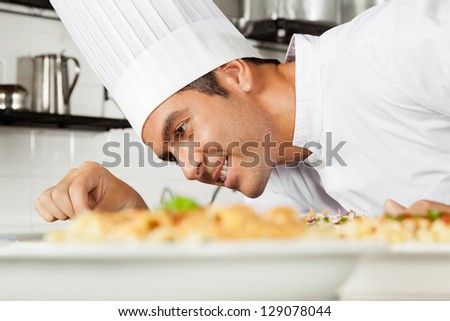 Happy male chef garnishing dish in commercial kitchen - stock photo