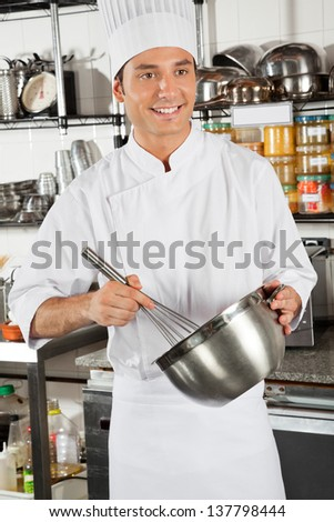 Happy male chef whisking egg in restaurant kitchen
