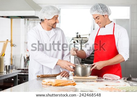 Happy male chefs discussing while preparing ravioli pasta at commercial kitchen counter - stock photo
