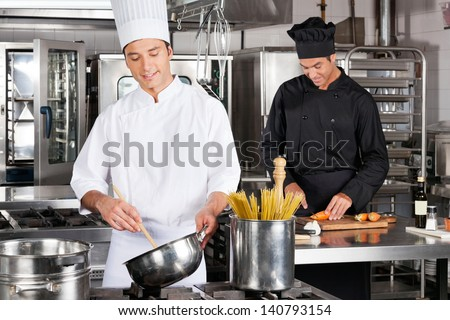 Happy male chefs preparing food in industrial kitchen