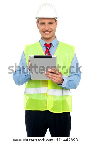 Happy male construction engineer with safety hat holding a wireless device