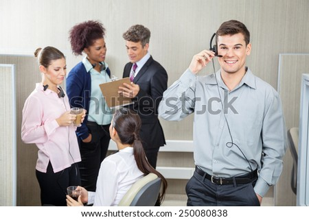 Happy male customer service representative using headphones with team discussing in background at call center - stock photo