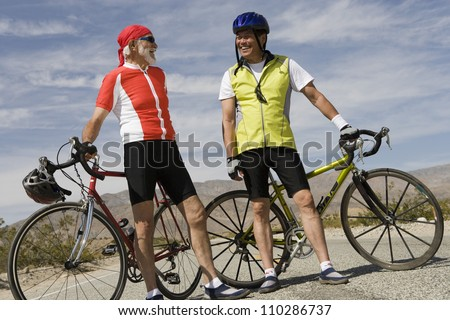 Happy male cyclists standing by their bicycles