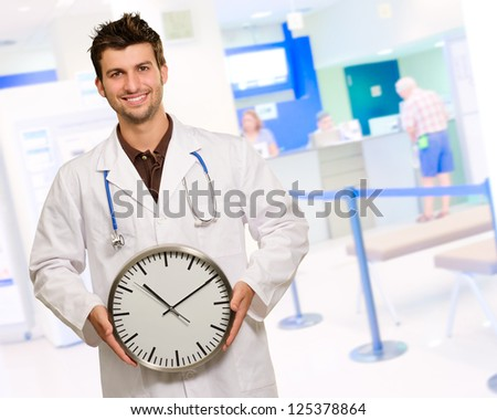 Happy Male Doctor Holding Clock, Indoors