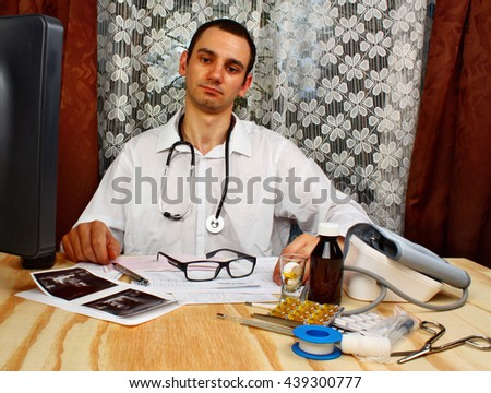 Happy male doctor looking at camera in medical office