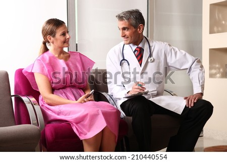 Happy male doctor speaking to woman patient about her health condition. - stock photo