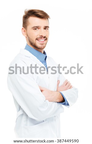 Happy male doctor standing with arms folded isolated on a white background - stock photo