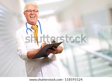 Happy Male Doctor Writing On Clipboard, Indoor