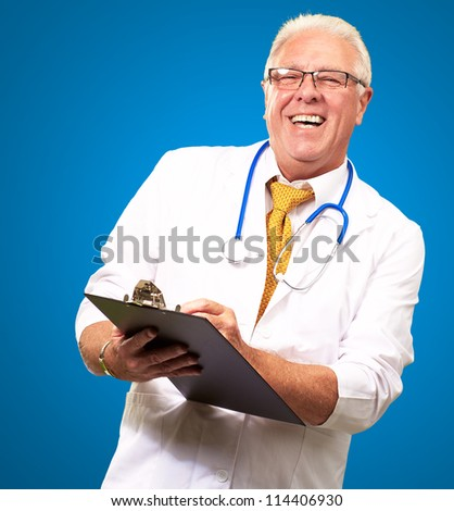 Happy Male Doctor Writing On Clipboard Isolated On Blue Background - stock photo