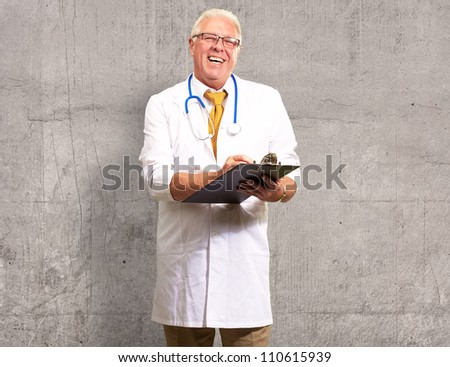Happy Male Doctor Writing On Clipboard On Wall