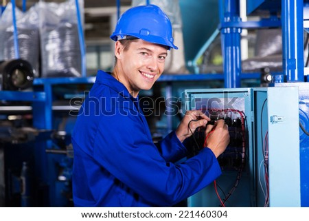 happy male electrician working on industrial machine - stock photo