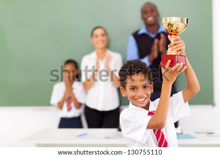 happy male elementary school student holding a trophy in classroom