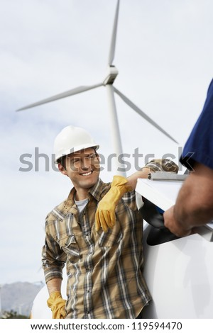 Happy male engineer at wind farm with man in foreground - stock photo