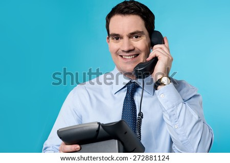 Happy male executive answering a phone call