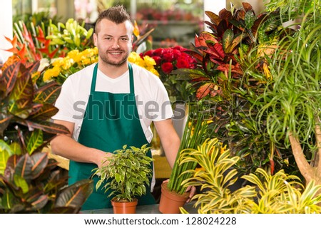Happy male florist working flower gardening shop market assistant - stock photo